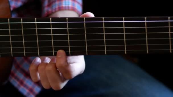 Chlapec se učí hrát na klasické kytaru. Zavři to. Prsty se dotýkají struny