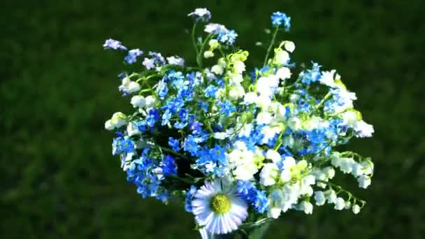 lily of the valleys, forget me nots and daisies wildflowers bouquet loop turning close up