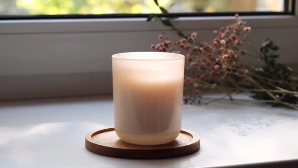 Hořící svíčka na parapetu s pohybem stínů a suchých květin na pozadí. Koncepce domácí atmosféra, aromaterapie, hořáky na přírodní olej, wellness terapie, čas na odpočinek, pro sebe.