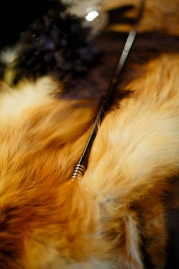 A black long mouthpiece with white stripes lies on the fur