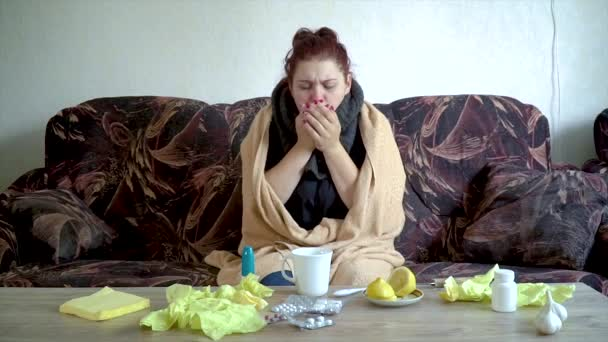 krankes kaukasisches Mädchen sitzt auf der Couch unter Decke und hustet