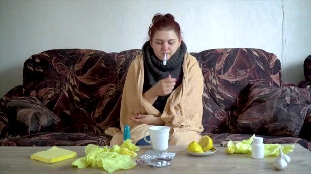 krankes kaukasisches Mädchen nimmt ihre Temperatur mit einem Thermometer zu Hause