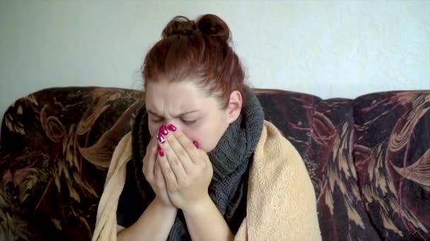 Nahaufnahme krankes kaukasisches Mädchen sitzt auf der Couch unter Decke und hustet