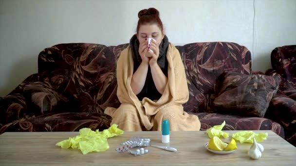krankes Mädchen sitzt auf der Couch unter einer Decke und trinkt heißen Tee