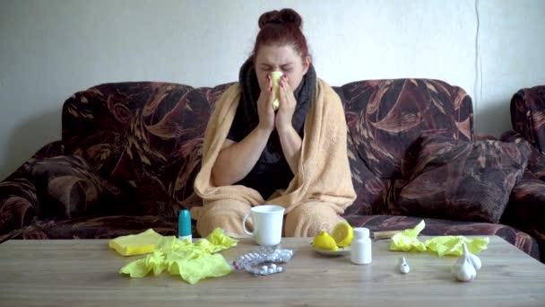 Kranke Kaukasierin pustet sich unter Decke in Papierserviette zu Hause die Nase