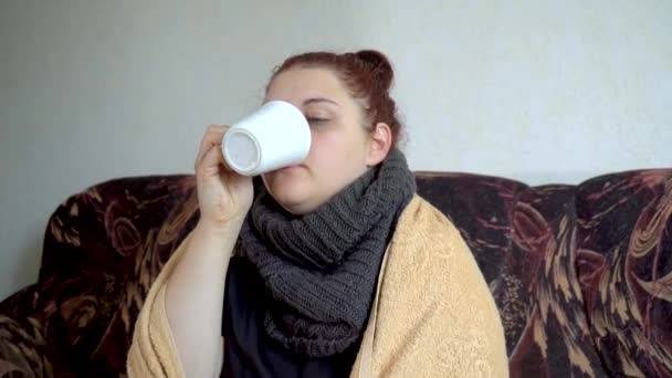 zblízka nemocný dívka sedí na gauči pod přikrývkou drží bílý šálek a pít horký čaj