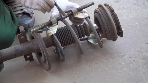 mechanik demontuje tlumič nárazů vyjmutý z auta