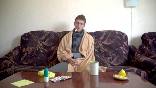 Kranker Kaukasier sitzt auf Couch unter Decke und misst seine Temperatur