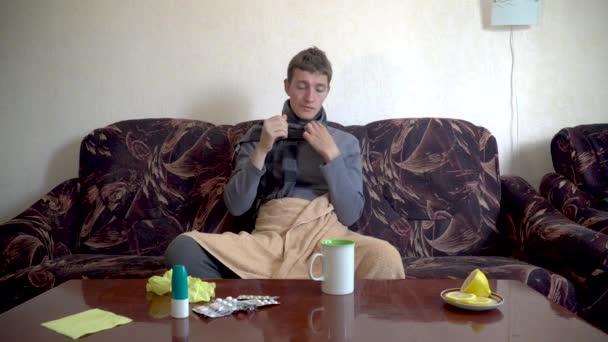 Kranker Kaukasier sitzt auf Sofa unter Decke, misst seine Temperatur und trinkt kalte Pillen