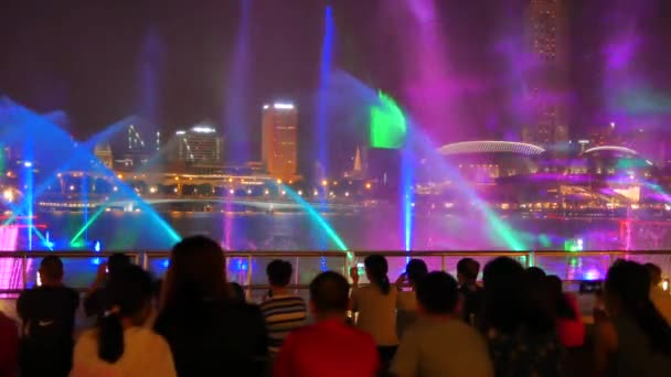 Blurred people on the foreground watch Spectra light and water show at the Event Plaza in Singapore