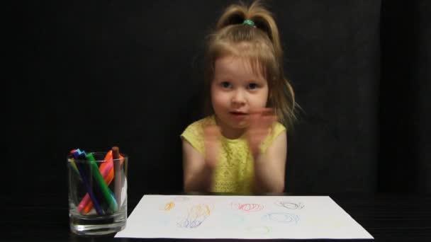 Kislány tapsol a kezét, és grimaces ül egy sötétszürke kanapén az asztalnál, miközben rajz