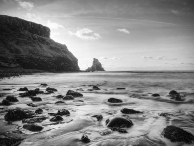 The rest of the day in rocky bay. Evening light on the rocks, boulders and cliff face of Talisker Bay, Isle of Skye
