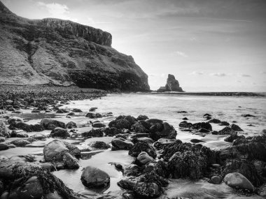 Tranquil stony bay in Scotland after sunset.  Slow shutter speed for smooth water level and dreamy effect