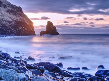 Cloudy evening on rocky shore at sunset. Sunset mirroring in  sea water and large cracked rocks with erosion marks Scotland, Sky Island, Talisker Bay.