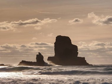 Evening Bay. Sharp rocks, black rounded boulders, stony beach, sand and dark sky.