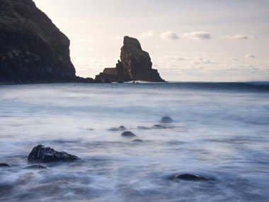 Sharp silhouette of a cliff against the background of sunset. Sea waves break on the rocks. Talisker bay, Scotland.
