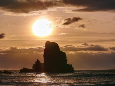 Beautifully shaped black boulders and a dramatic fiery sunset and a stony beach