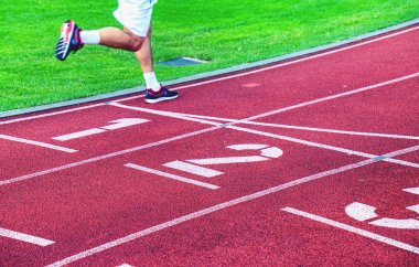Male athletes are running on outdoor stadium track. Red rubber running tracks with numbers and wwhite lines of the stadium.