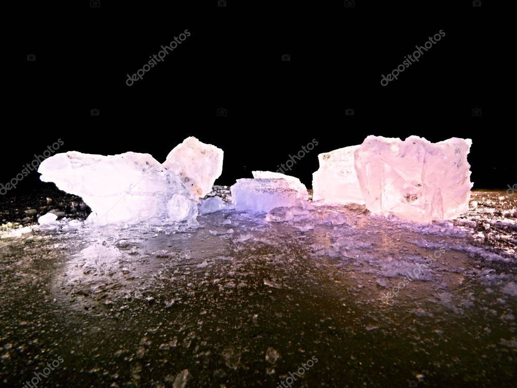 Detail photo of real ice crystals:. Icy stone laying on black shining and broken ice surface.