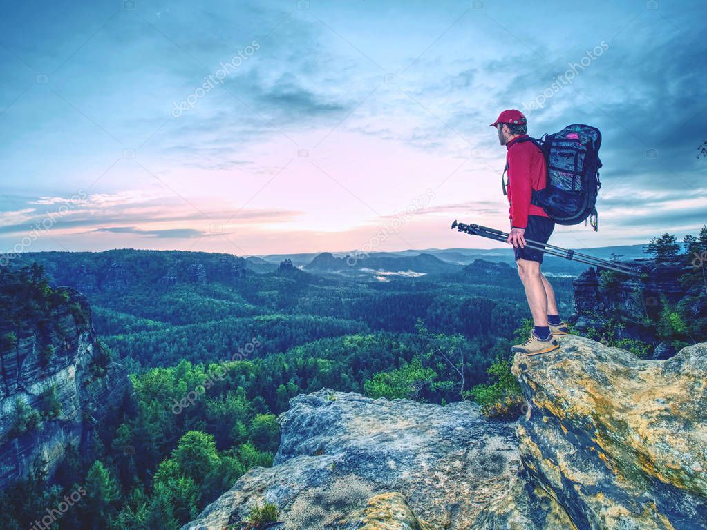 Amateur photographer. Tourist photographer with  big camera log and basalt tripod in hand on top of  mountain at sunset. Travel outdoors during summer