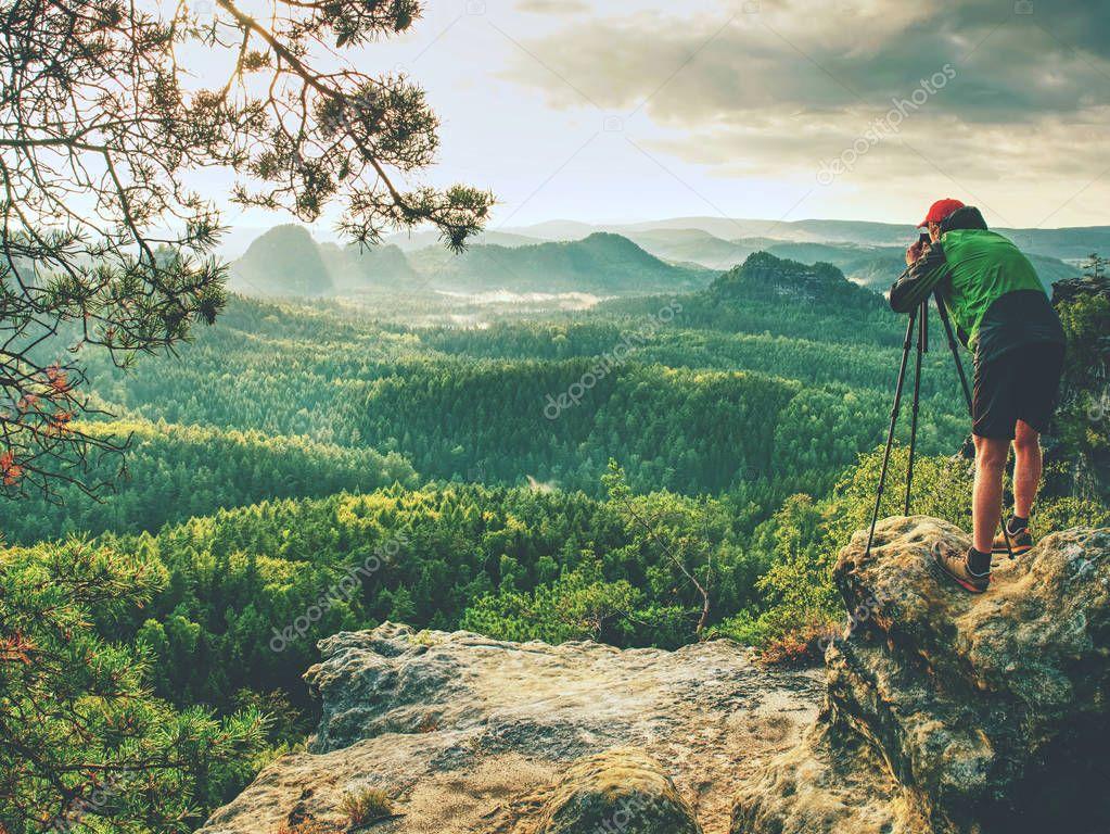Landscape photographer prepare camera to takes impressive photos of misty fall mountains. Tourist photographer at sharp rocky edge