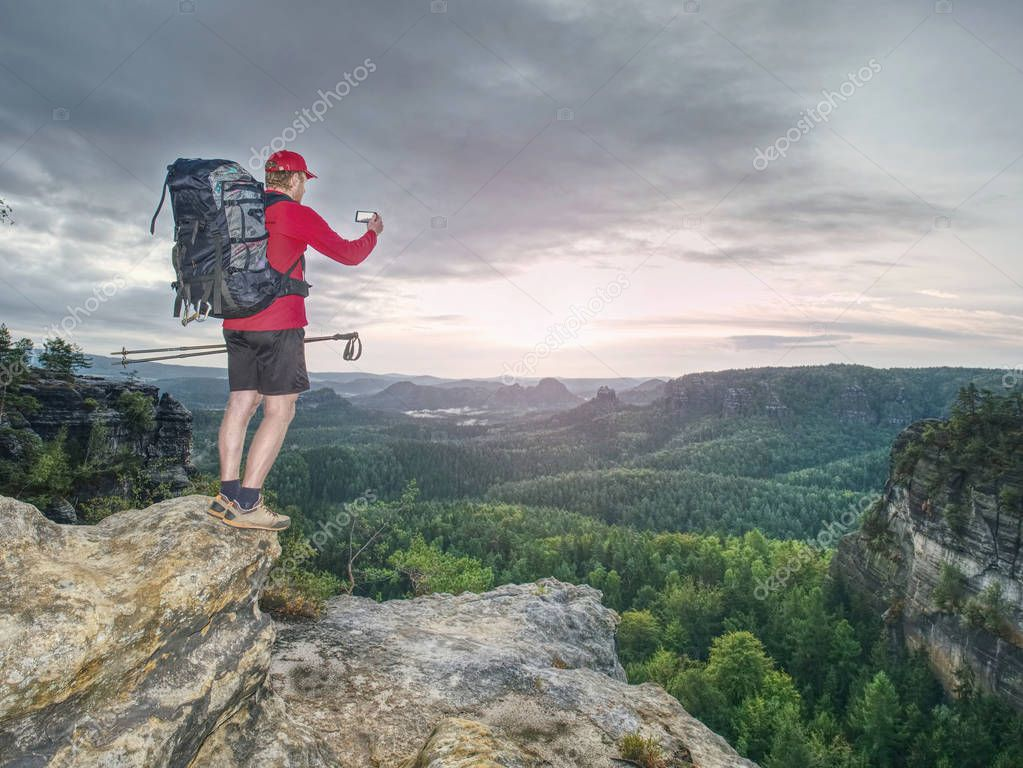 Photographer shooting stunning landscape on a sunny day in nature. Traveler photographer capturing amazing landscape in high mountain.
