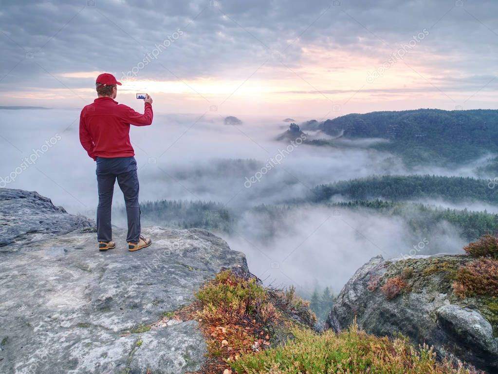 Tall man hiking in autumn nature. Bad Schandau range, Germany, 21st of August 2018.  Tourist on the mountain taking photos with touch screen smartphone