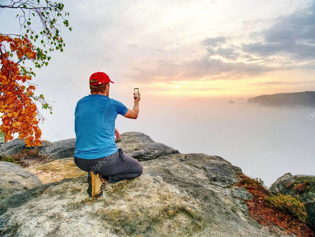 Hiker takes selfie photo, fall nature adventure. Bad Schandau range, Germany, 21st of August 2018.   Man sit on stone on mountain sumit  Daybreak horizon above milky fog.