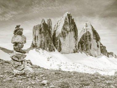Stack of stones with mountain landscape along Alps peaks, Tre Cime di Lavaredo rocks Dolomites in Italy