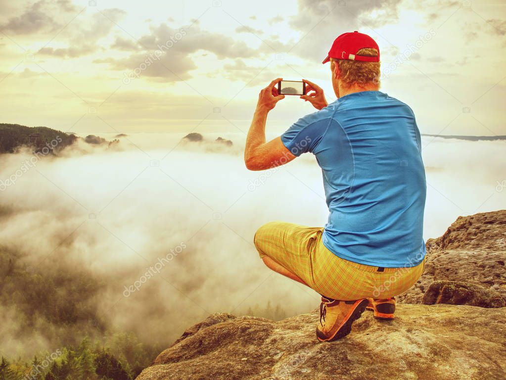 Tall man hiking in autumn nature. Tourist on the mountain taking photos with touch screen smartphone