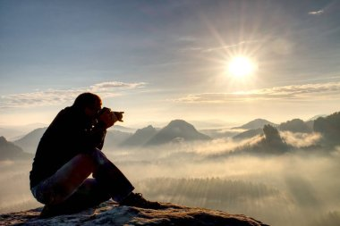 Man photographer during hike. Photographer taking photos outdoor by dslr camera. Travel lifestyle