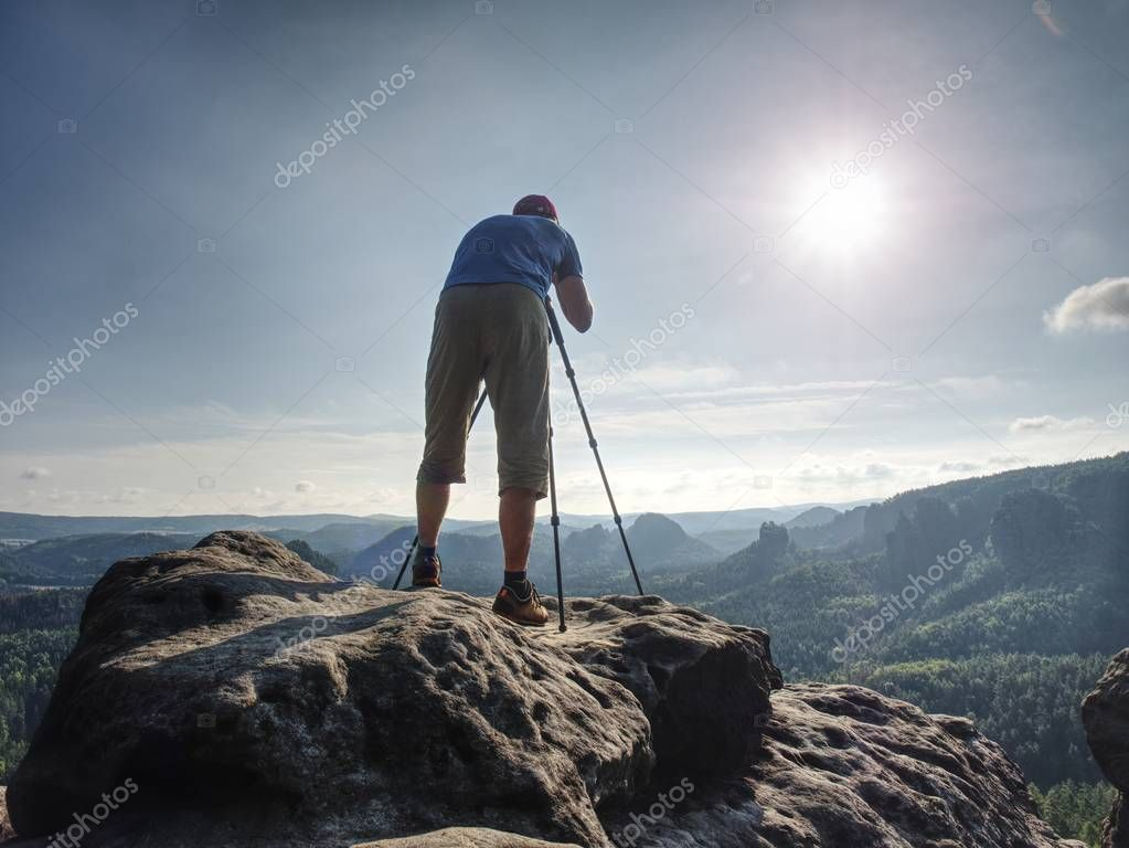 Nature  photographer hold tripod with camera. Man at sunrise at open view on mountain peak blue sky