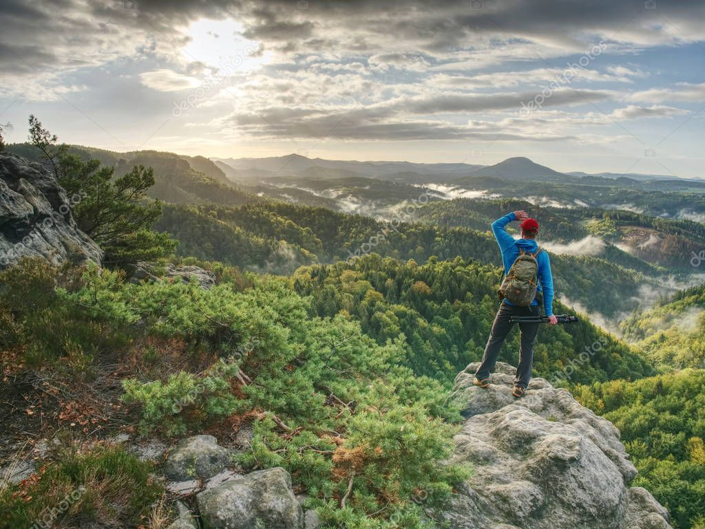 Freelancer create nature photos. Professional photographer takes photos with camera on tripod on rocky peak. Dreamy fogy landscape