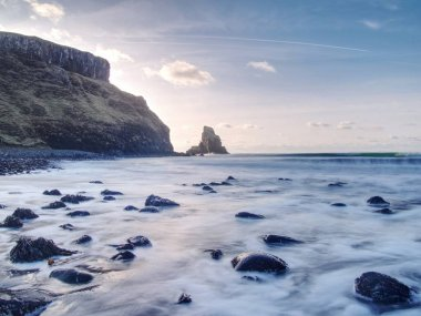 Sea stack sharp silhouette by sunset sky. Evening light on the rocks, boulders and cliff face of Talisker Bay, Isle of Skye