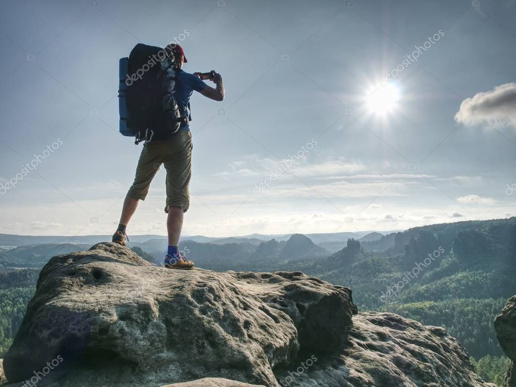 Nature photographer working with camera and tripod on peak of rock. Wild nature park with deep forests in valleys