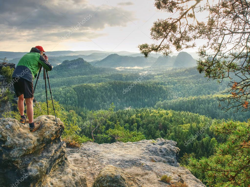Photographer or videographer  traveler with heavy backpack and tripod in hand is preparing for art work. Artist in pure nature take impressive landscape photos.