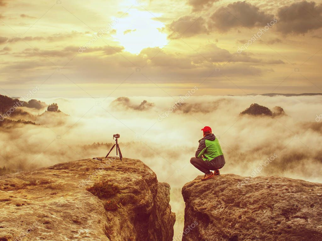 Happy photo enthusiast enjoy photography of fall daybreak in nature on cliff on rock. Artist in pure nature take impressive landscape photos