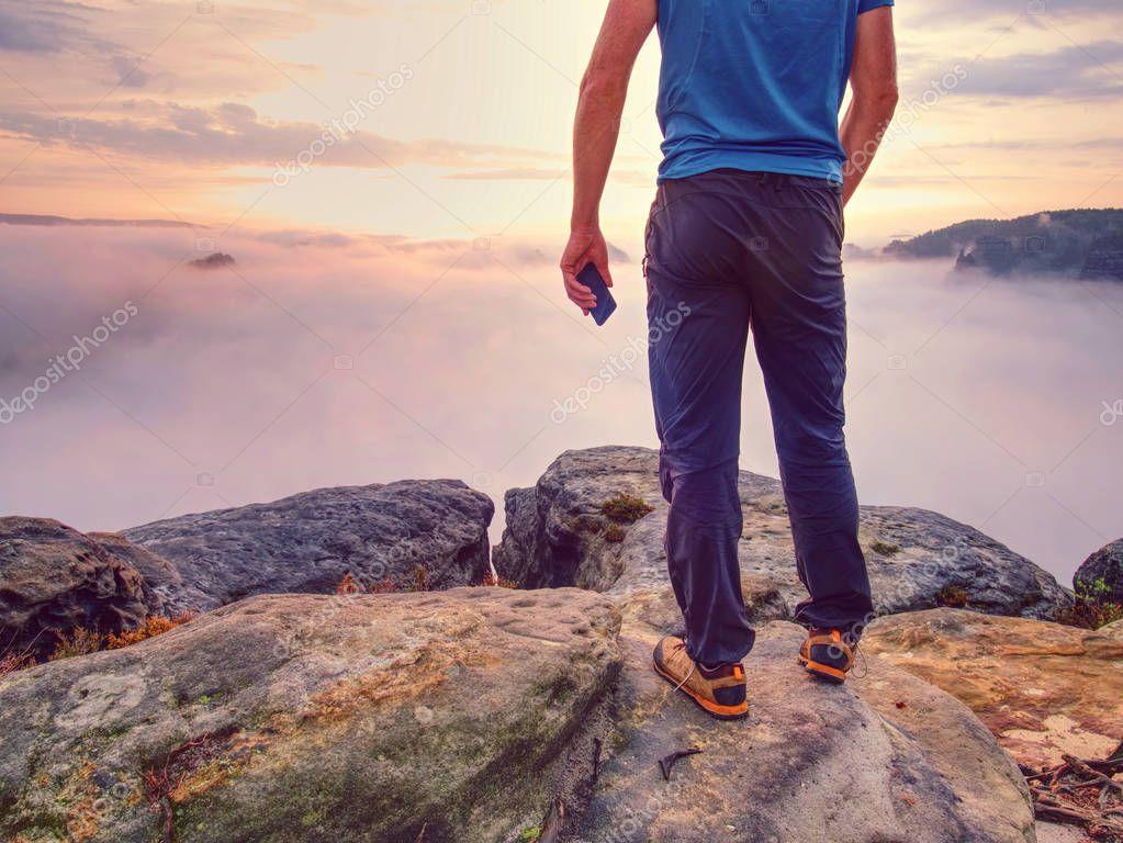 Hiker takes selfie photo, fall nature adventure. Man sit on stone