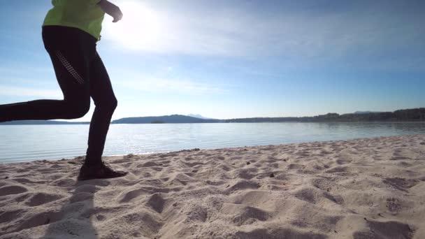 Mann in Fitnesskleidung läuft am Sandstrand entlang. Schlanker Mann mittleren Alters, der bei Sonnenuntergang an der Küste entlang läuft. Zeitlupe