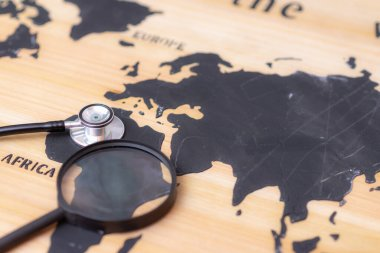 Stethoscope and magnifying glass on wooden world map background. Selective focus.