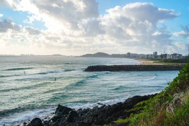 Stunning view of the Pacific Ocean and surfers catching waves in Tallebudgera Creek, visible from the Burleigh Head National Park on Gold Coast, Australia.