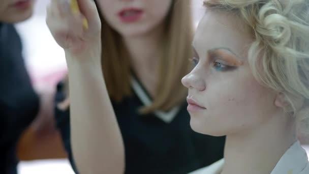 Maskérka vysvětlují studentovi používání kosmetiky, vytváření stylu retro vzhled
