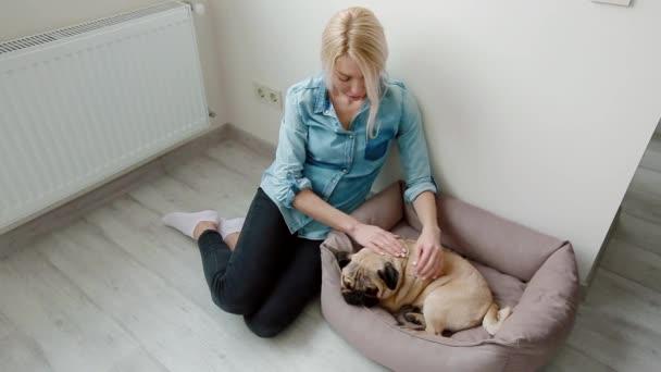 Fiatal nő kisállat neki kutya ül a földön