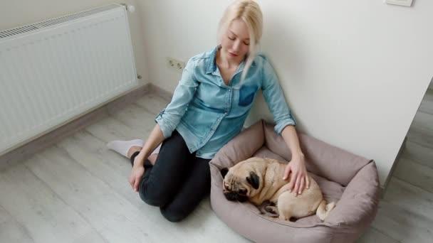Fiatal nő simogatta a lány kutya ül a földön