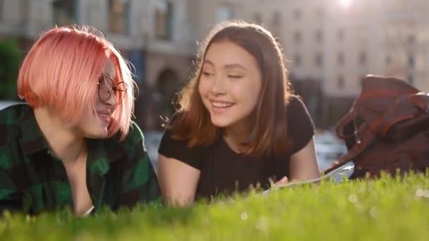 Dvě studentky na trávě s knihou