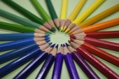 Closeup colorful pencil on green paper background