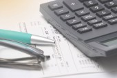 Calculator, receipt, spectacles and pen on workstation. Financial and tax concept