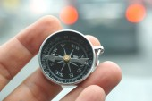 Hand holding a magnetic compass over nature background