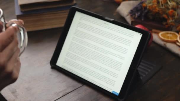 Frau hält Becher mit Glühwein in beiden Händen und liest Buch auf Tablet.