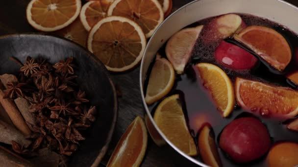 Příprava svařeného vína. Červené víno bublá na talíř s citróny, pomeranči, jablky. Anýzové hvězdy a skořicové hole v hnědé dřevěné míse v popředí. Zavřít horní pohled.
